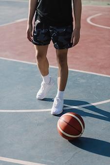 Sport- en recreatieconcept een jonge sportman die zwarte outfits en witte schoenen draagt en in de buurt van een basketbal staat