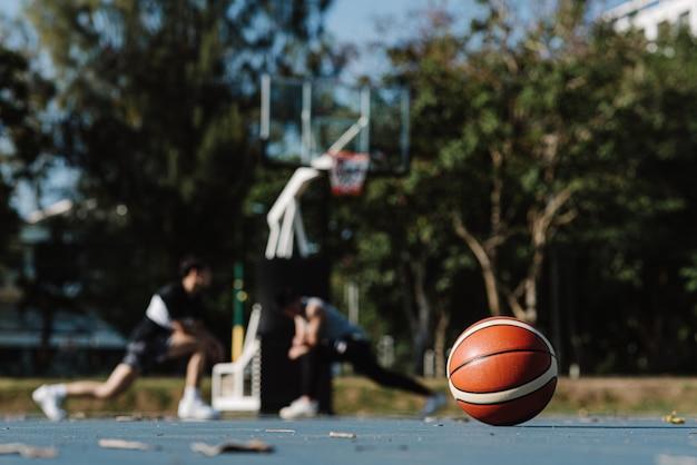 Sport- en recreatieconcept een ronde basketbal die op de vloer van een basketbalveld ligt.