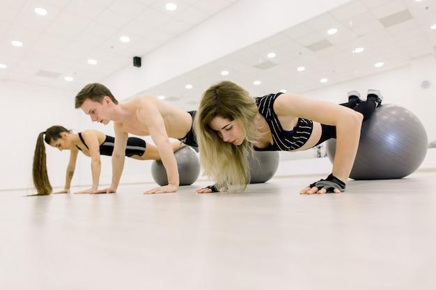 Sport, fitness, levensstijl en mensenconcept - glimlachende man en twee vrouwen die met oefeningsbal uitwerken in gymnastiek