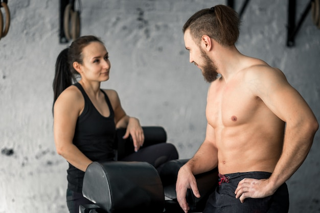 Sport, fitness, levensstijl en mensenconcept - glimlachende man en vrouw in gymnastiek
