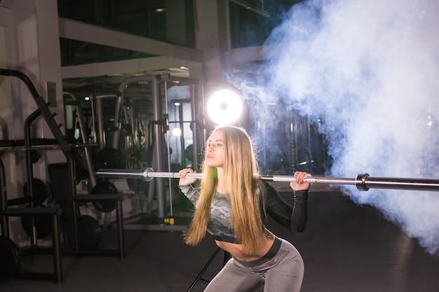Sport, fitness, opleiding en geluk concept - sportieve vrouw met barbell in sportschool
