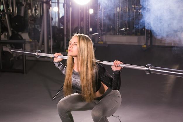 Sport, fitness, opleiding en geluk concept - sportieve vrouw met barbell in sportschool.