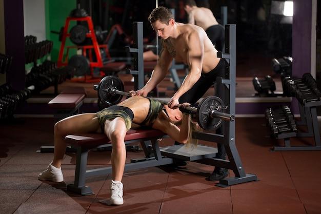 Sport, fitness, teamwork, bodybuilding en mensenconcept - jonge vrouw en persoonlijke trainer met de spieren van de barbellverbuiging in gymnastiek