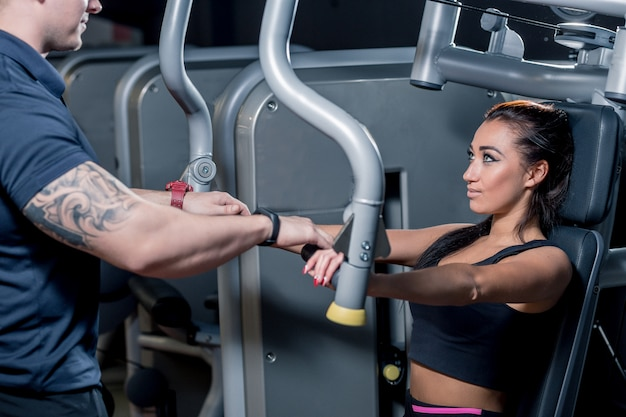 Sport, fitness, teamwork en mensen concept. jonge vrouw buigen spieren op gym machine en personal trainer met klembord