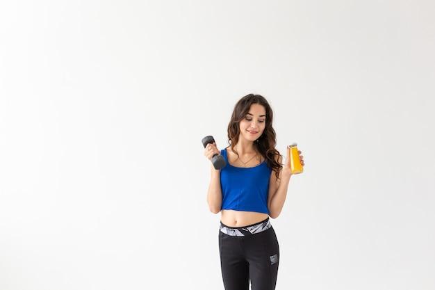 Sport, gezonde levensstijl, mensen concept - jonge vrouw met een halter in haar hand en een fles sap in een andere hand op witte achtergrond met kopie ruimte