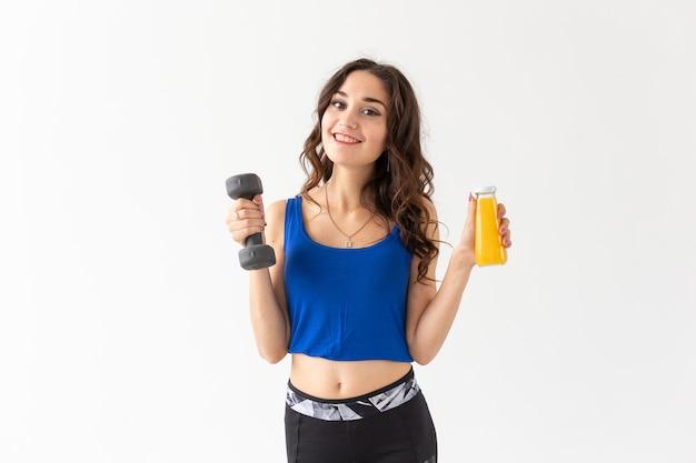 Sport, gezonde levensstijl, mensen concept - jonge vrouw met een halter in haar hand en een fles sap in een andere hand op witte achtergrond