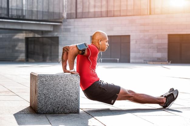 Sport is leven. sterke aardige man die zijn spieren ontwikkelt tijdens het sporten