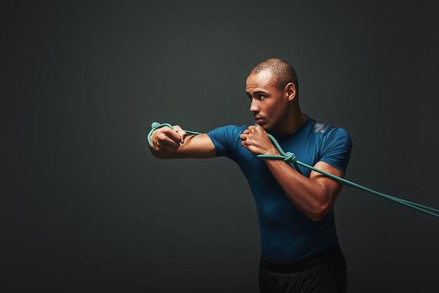 Sport is mijn lifestyle-sporter die traint met een weerstandsband op een donkere achtergrond