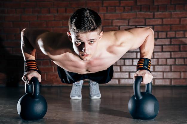 Sport. jonge atletische man doet push-ups. gespierde en sterke man oefenen.