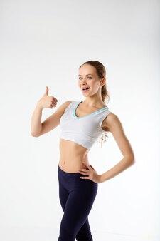 Sport jonge vrouw met perfect lichaam toon ok gebaar, fitness
