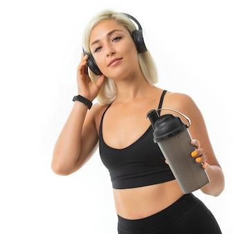 Sport kaukasisch blondemeisje met oortelefoons doet sporten en drinkt water van sportfles