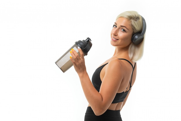 Sport kaukasisch blondemeisje met oortelefoons doet sporten, glimlacht en drinkt water van sportfles