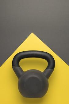 Sport kettlebell op een gele en donkergrijze achtergrond. sportieve levensstijl. kleuren 2021.