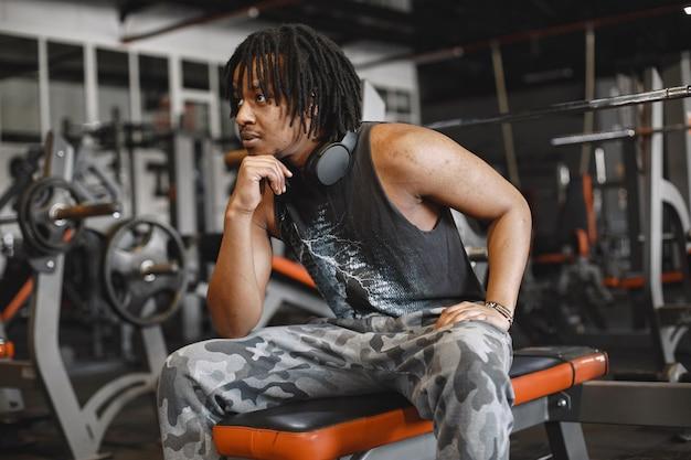 Sport man in de sportschool. een zwarte man voert oefeningen uit. man in een zwart t-shirt
