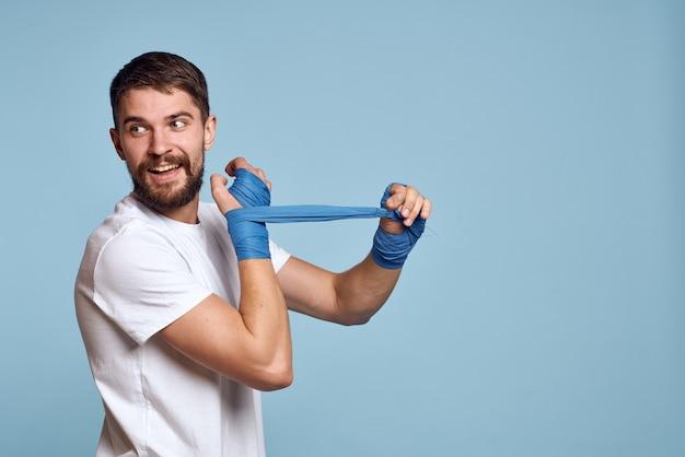 Sport man in wit t-shirt boksbandages op handen blauwe geïsoleerde ruimte oefeningstraining.