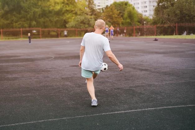 Sport man spelen met een voetbal in het stadion