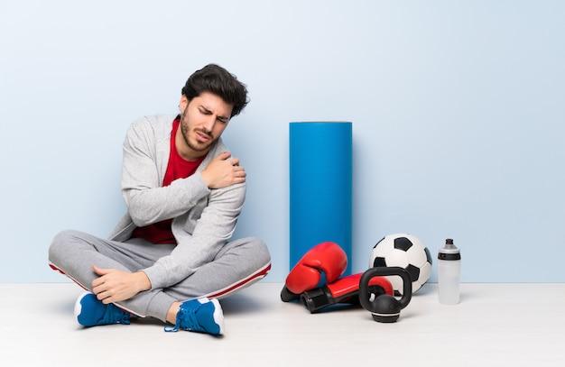 Sport man zittend op de vloer die lijden aan pijn in de schouder voor een inspanning