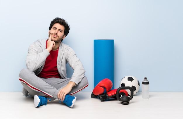 Sport man zittend op de vloer op zoek naar voren