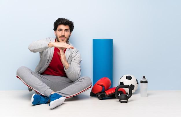 Sport man zittend op de vloer time-out gebaar maken