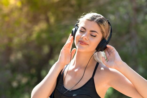 Sport meisje doet sport in openlucht luisteren naar muziek met een koptelefoon