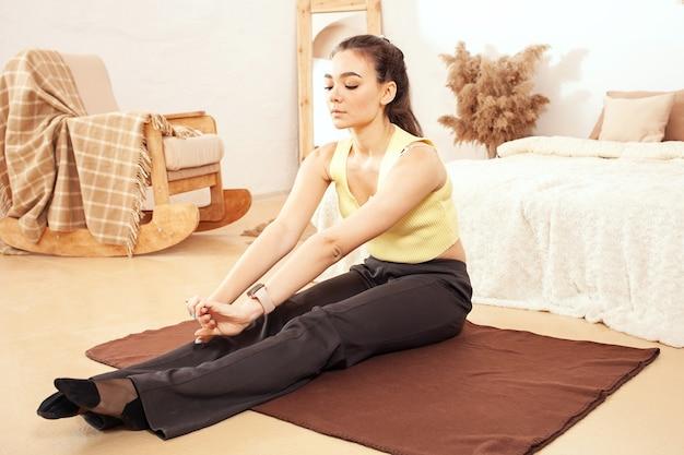 Sport meisje. een gezonde leefstijl. een vrouw oefent wel op de mat, 's ochtends thuisquarantaine