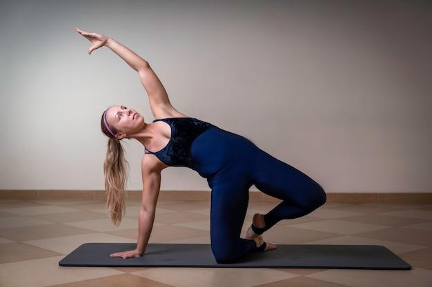 Sport meisje houdt zich bezig met uitrekken, leunend op knie en hand