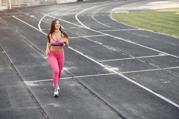 Sport meisje in een roze uniform loopt in het stadion