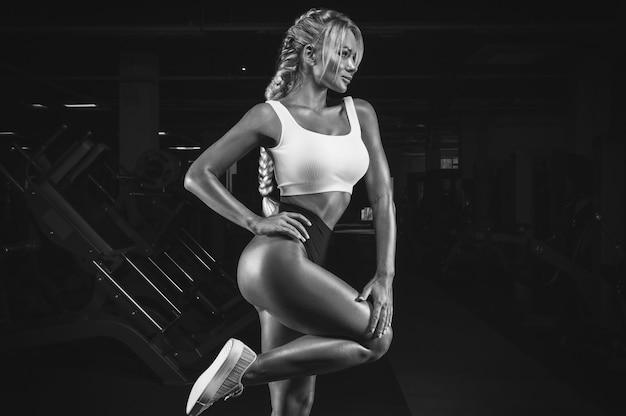 Sport meisje in een top en slipje is aan het trainen in de sportschool. fitnessconcept