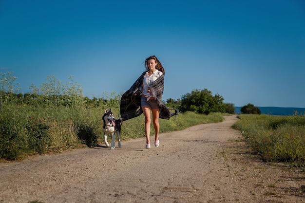 Sport meisje loopt met een hond de siberische husky op de weg