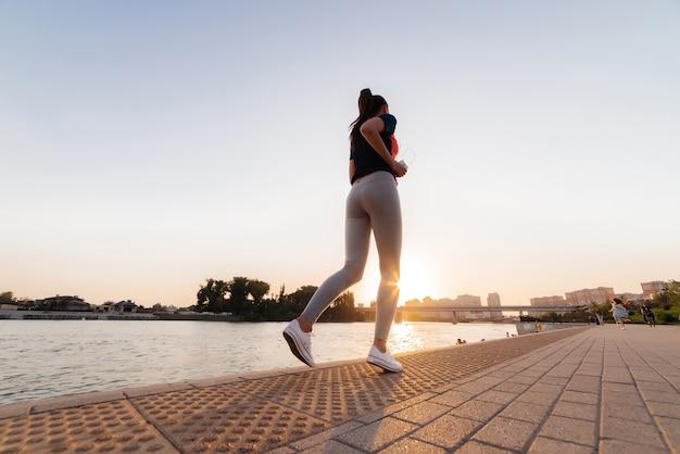 Sport meisje op een run in het park, in de buurt van de rivier, op de achtergrond van een bos en een brug. ochtendgloren