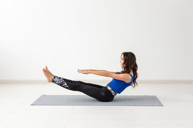 Sport, mensen concept - jonge vrouw swingende pers door statica oefeningen