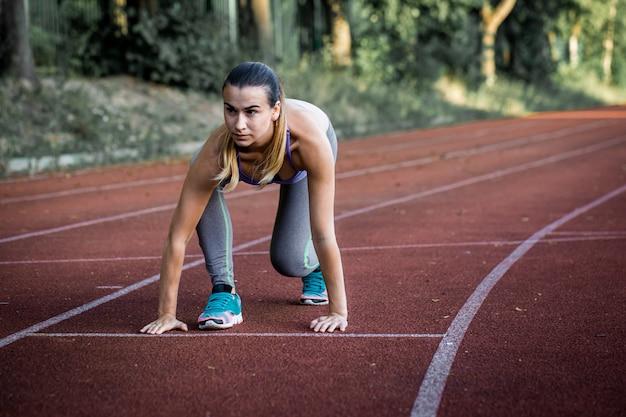 Sport mooi meisje op de loopband klaar om een groot stadion, close-up te runnen
