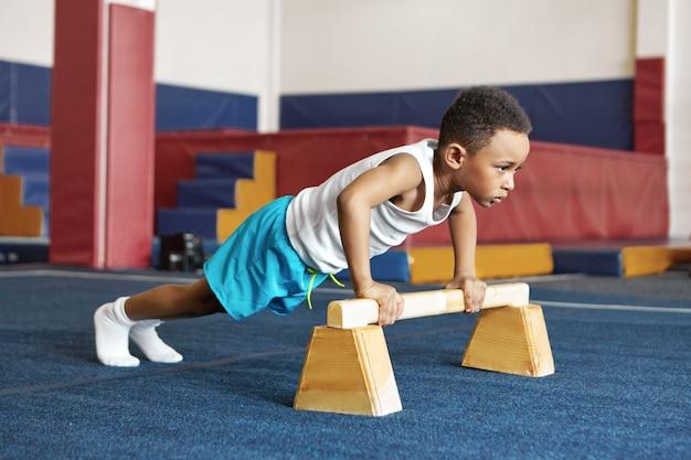 Sport, motivatie en krachtconcept. binnenbeeld van ernstig gedisciplineerd zwart kind met donkere huid