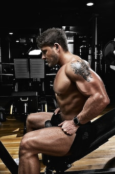 Sport motivatie. sportschool theater. gespierde man bodybuilder doen oefeningen met halters in de sportschool. atletisch lichaam, gezonde levensstijl, fitnessmotivatie, positief lichaam.