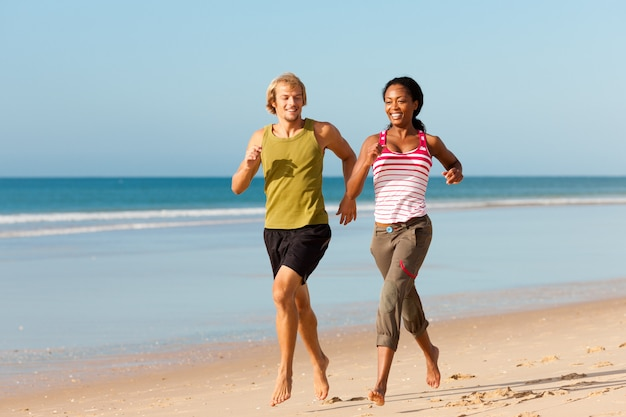 Sport paar joggen op het strand