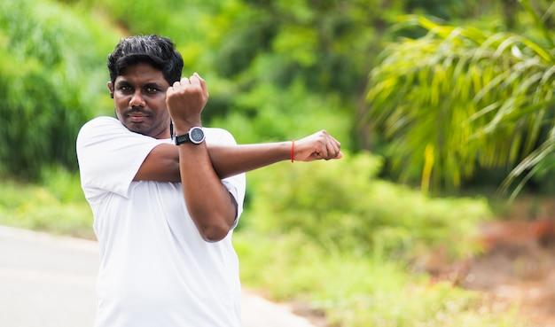 Sport runner zwarte man dragen horloge hij lichaam opwarmen armen spieren voor het hardlopen