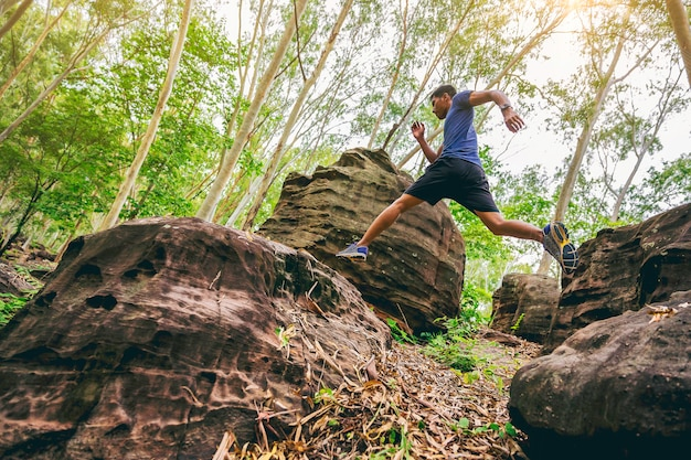 Sport running man in cross country trail run springen op het rotsachtige bergpad