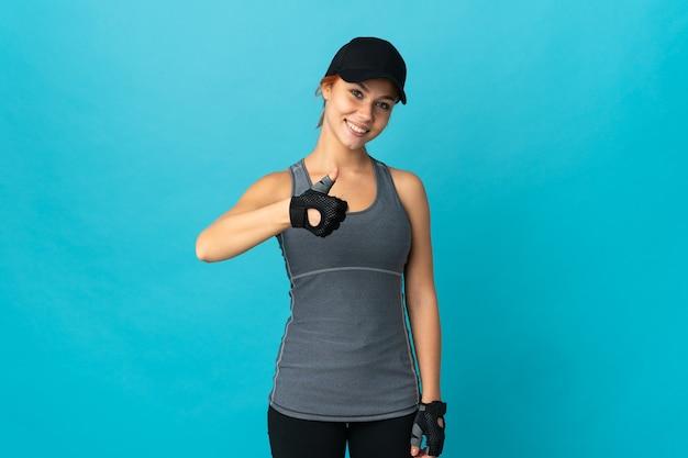 Sport russische vrouw geïsoleerd op blauw met een duim omhoog gebaar