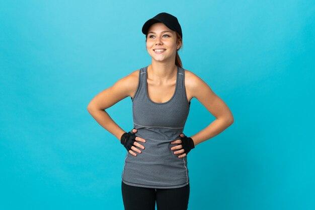 Sport russische vrouw geïsoleerd op blauw poseren met armen op heup en glimlachen