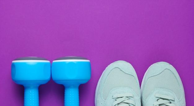 Sport sneakers, blauwe plastic halters op een paarse achtergrond.