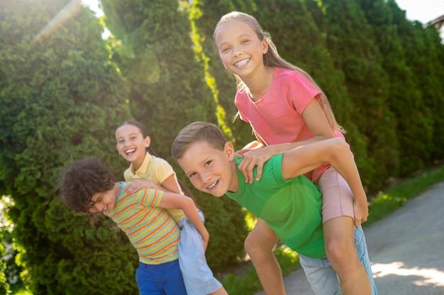 Sport spellen. twee energieke jongens die lachende langharige meisjes op hun rug houden in een groen park op zonnige dag