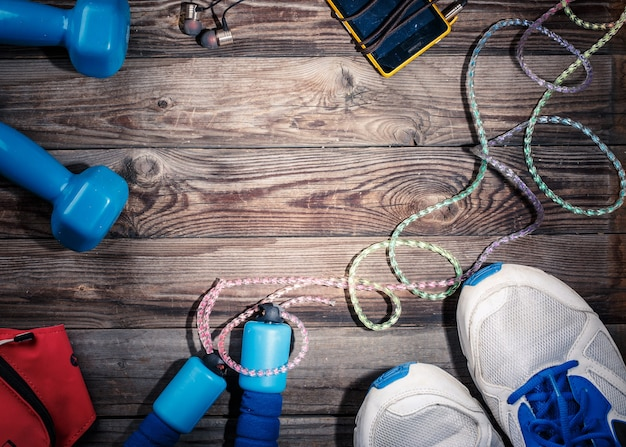 Sport spullen op houten tafel, bovenaanzicht. lichtvlek in het midden van houten tafel met lege ruimte voor tekst, logo of iets anders.