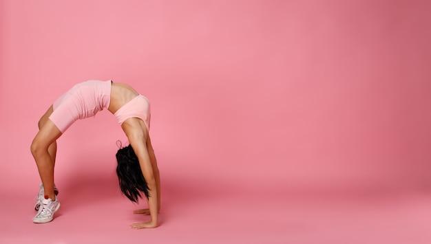 Sport tienermeisje praktijk oefening brug backbend, doen mode macht poses. 12 jaar oud aziatisch jeugdatleet dat een pastelroze fitnessbroek draagt over de volledige lengte van een roze achtergrond