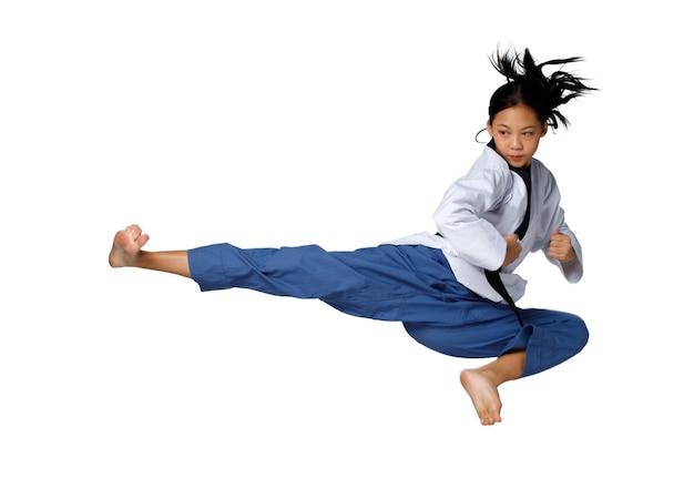 Sport tienermeisje springt hoog en schopt als zweven in de lucht. 12-15 jaar oud aziatisch jeugdatleet kind draagt taekwondo karata uniform over witte achtergrond geïsoleerd volledige lengte