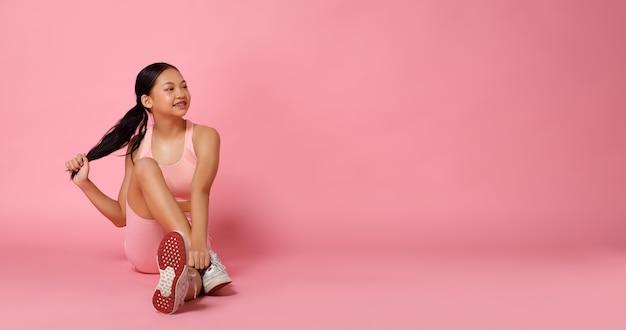 Sport tienermeisje zit en glimlacht naar links, doet fashion power poses. 12 jaar oud aziatisch jeugdatleet dat een pastelroze fitnessbroek draagt over de volledige lengte van een roze achtergrond
