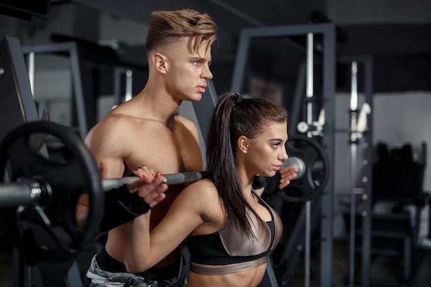 Sport, training, fitness, lifestyle en mensen concept - jonge vrouw met personal trainer buigende rug en buikspieren op de bank in de sportschool. hoge kwaliteit foto