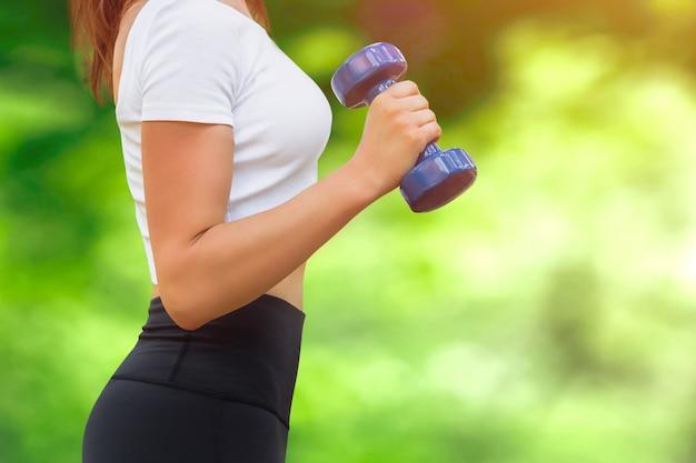 Sport trainingsconcept. meisje in wit t-shirt met een halter in haar hand
