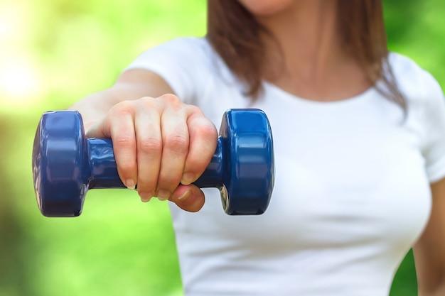 Sport trainingsconcept. vrouwelijke hand houdt een blauwe halter