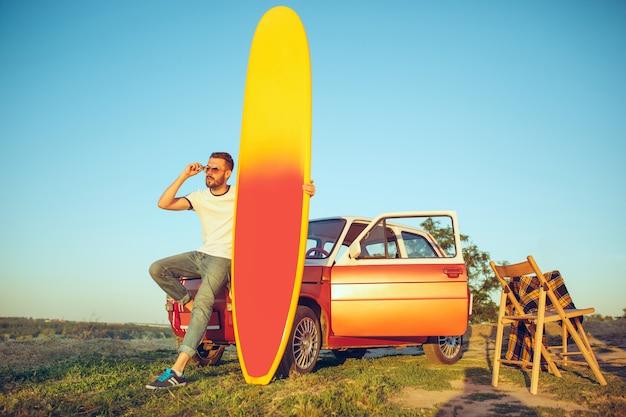 Sport, vakantie, reizen, zomerconcept. blanke man staande in de buurt van auto met surfplank op aard