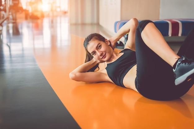 Sport vrouw doen zit in fitness sport training club met sportuitrusting